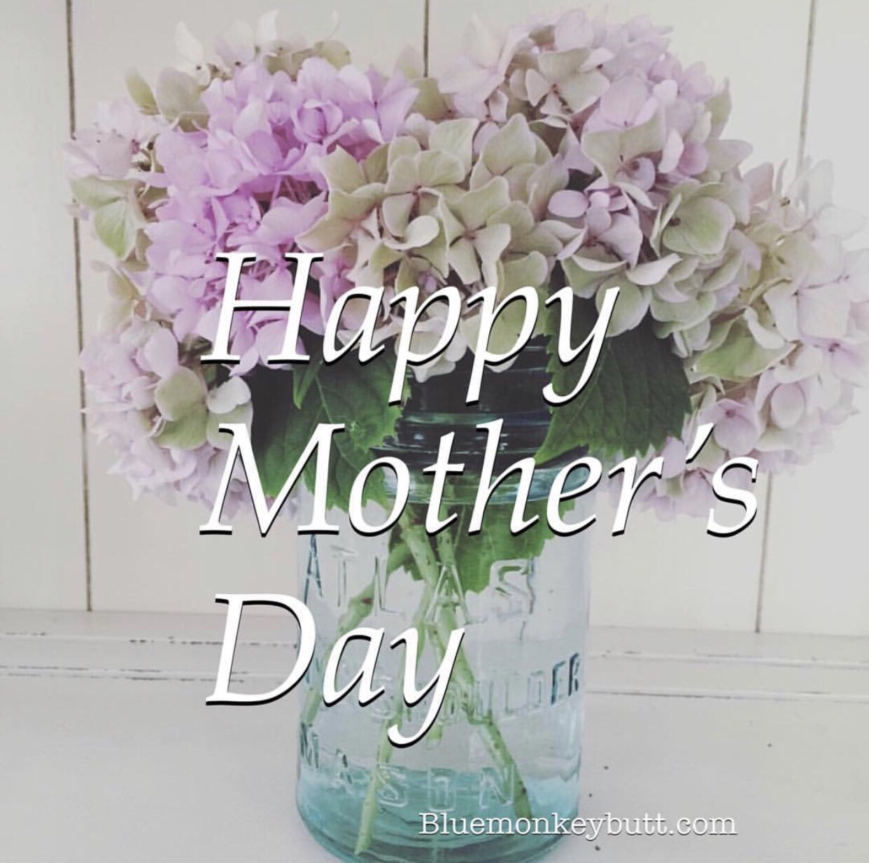 Flowers in a mason jar with Happy Mother's Day superimposed over photo